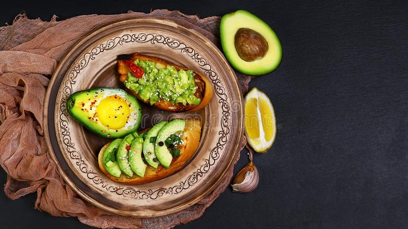 Healthy lunch snack, three delicious avocado sandwiches, fresh sliced avocados, garlic, lemon, on an earthenware plate copy space. On a black stone background stock photo