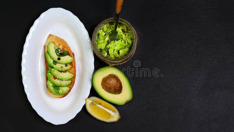Healthy lunch snack, three delicious avocado sandwiches, fresh sliced avocados, on an plate, copy space on a black stone backgroun royalty free stock images