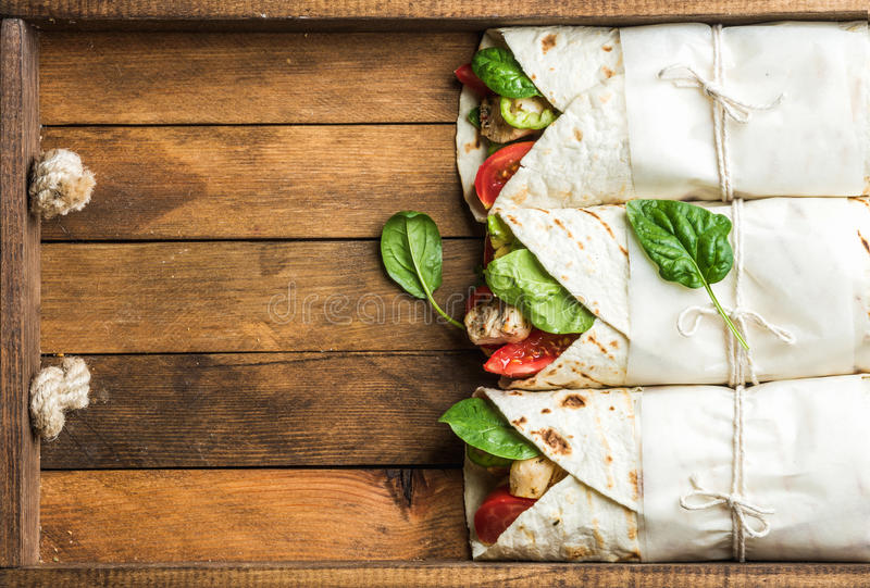 Healthy lunch snack. Tortilla wraps with grilled chicken fillet and fresh vegetables royalty free stock photo