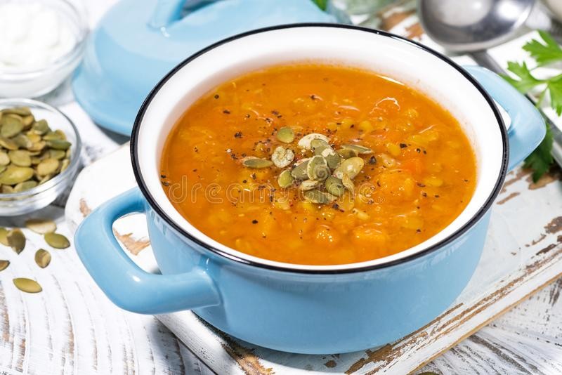 Healthy lunch. spicy pumpkin soup with lentils in a saucepan. Closeup top view stock photography