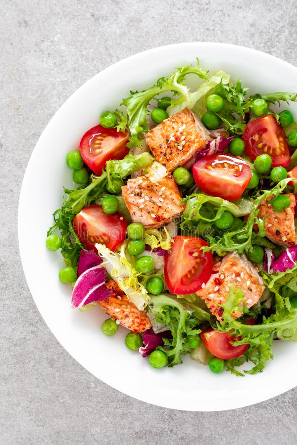 Healthy lunch vegetable salad with baked salmon fish, fresh green peas, lettuce and tomato stock image