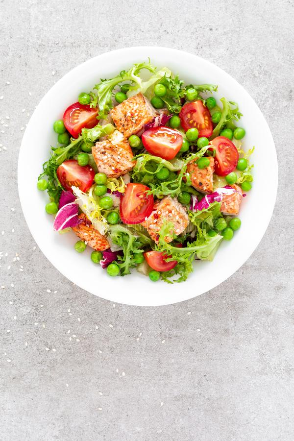 Healthy lunch vegetable salad with baked salmon fish, fresh green peas, lettuce and tomato royalty free stock photos