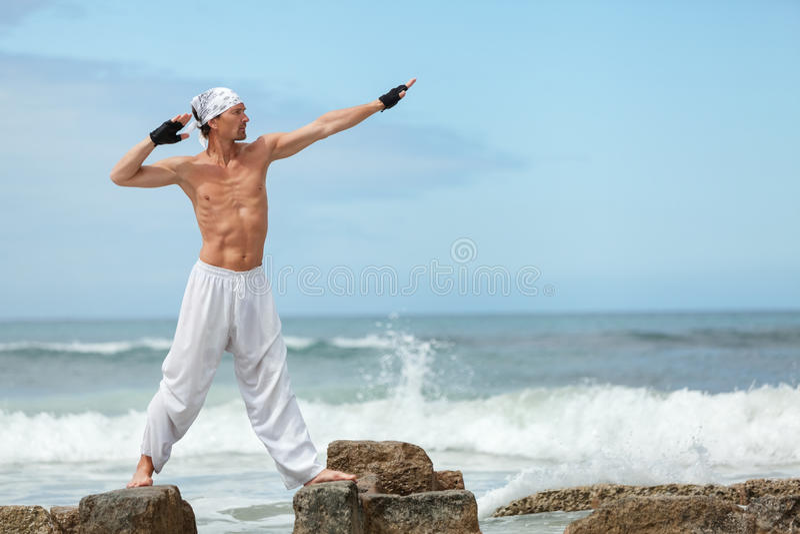 Healthy man doing pilates yoga meditation on beach summer stock photos