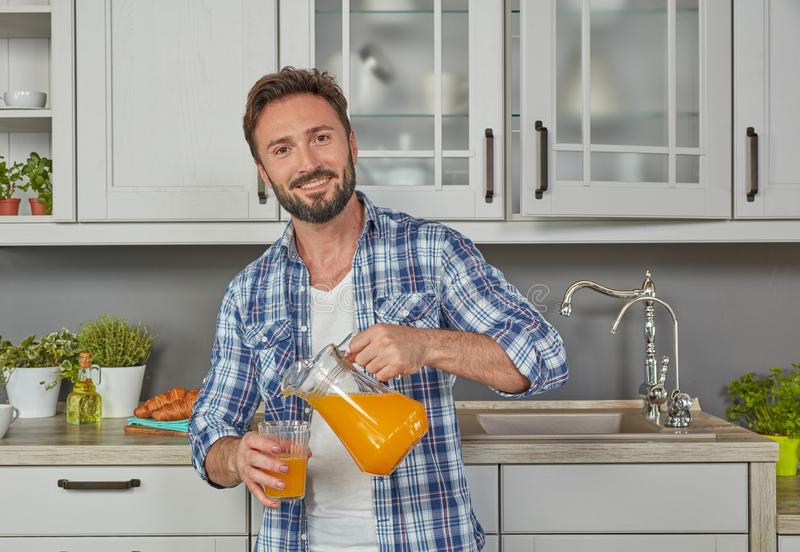 Healthy man pouring orange juice stock images