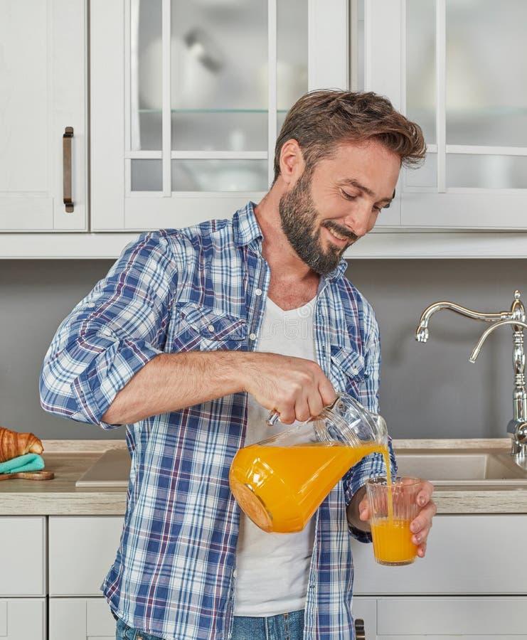 Healthy man pouring orange juice stock photos