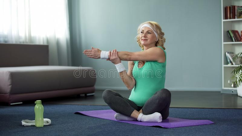 Healthy mature female doing fitness exercises on yoga mat, training at home royalty free stock photos