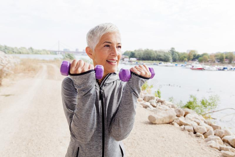 Healthy Mature Woman Exercise With Weights royalty free stock image