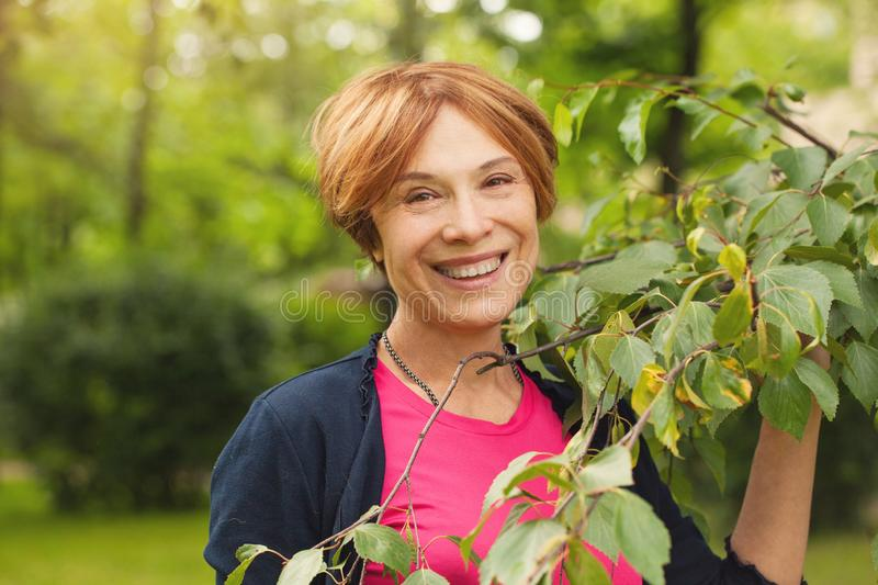 Healthy mature woman having fun with green leaves outdoor. Beautiful model 60 years old royalty free stock image