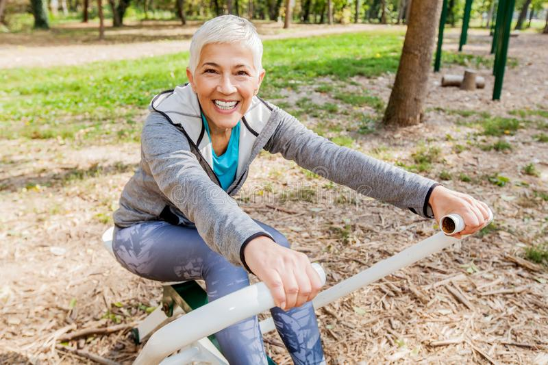 Healthy Mature Woman Practicing At Outdoor Gym royalty free stock image