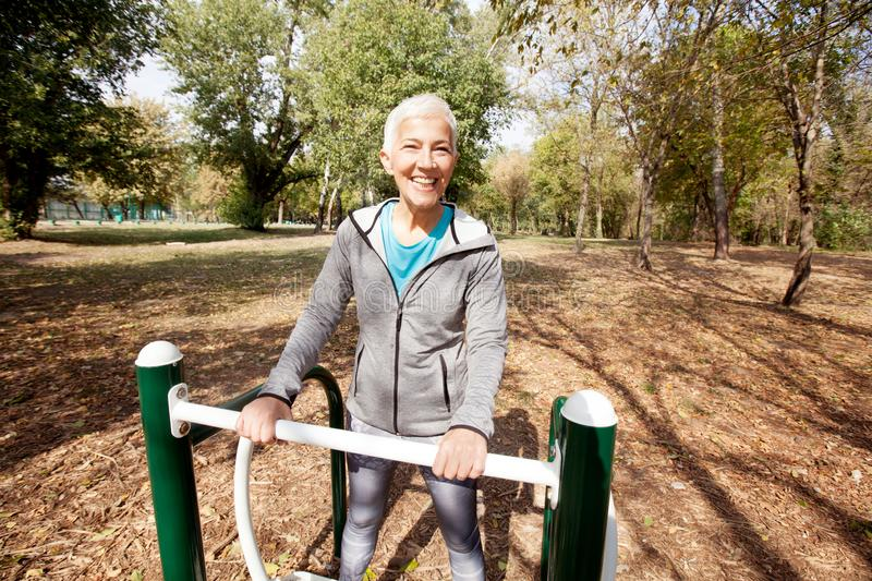 Healthy Mature Woman Workout At Outdoor Gym In Forest royalty free stock photo