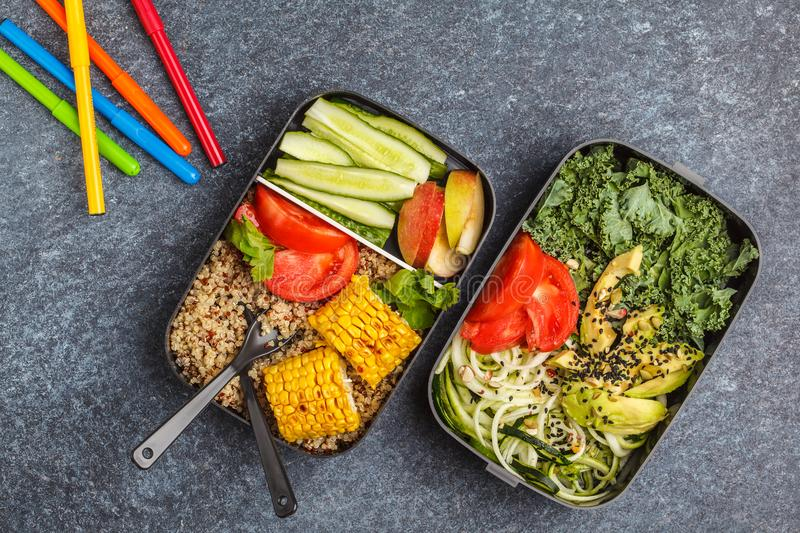 Healthy meal prep containers with quinoa, avocado, corn, zucchini noodles and kale. Takeaway school food. Dark background, top vi stock photo
