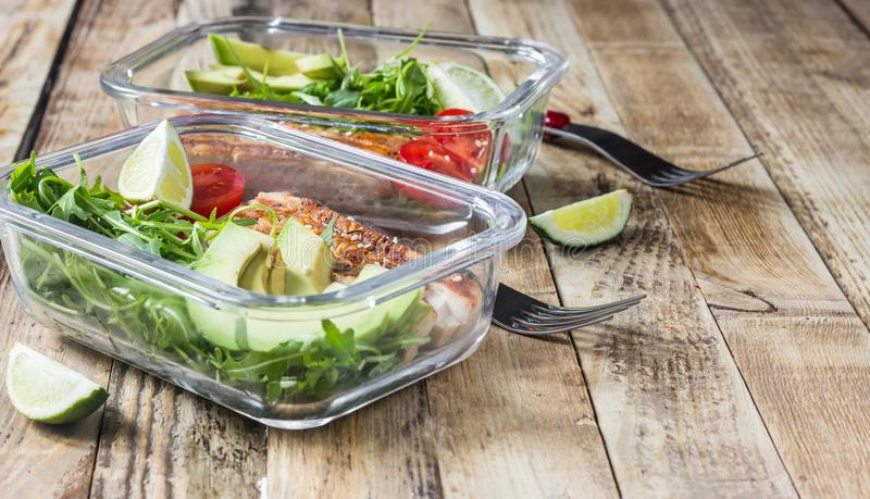 Healthy meal prep containers with rukola, turkey grill, tomatoes and avocado. Selective focus stock photos