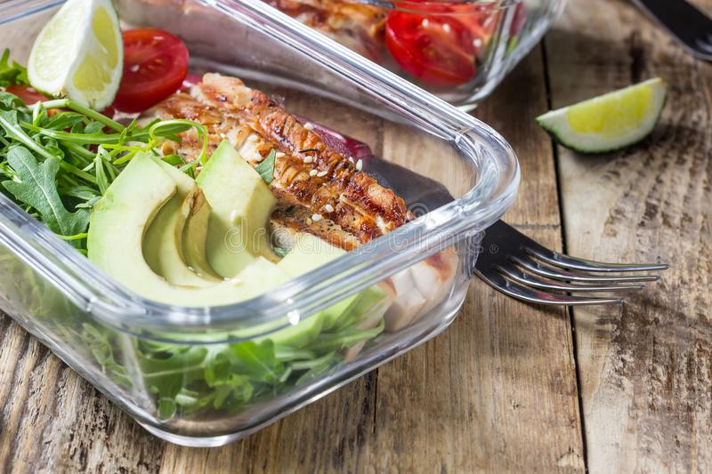 Healthy meal prep containers with rukola, turkey grill, tomatoes and avocado. Selective focus stock images