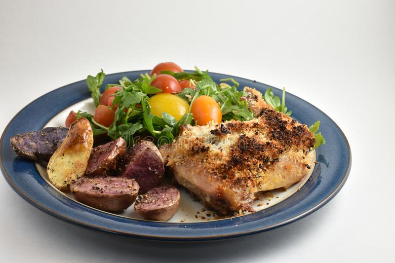 Healthy meal with roaster herb crusted chicken, multicolor fingerling potatoes, and arugula salad with heirloom tomatoes and lemon. Dressing. Served on blue rim stock image
