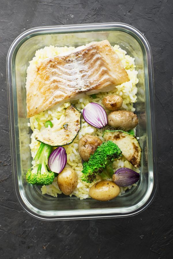 A healthy meal for a snack is a lunch box. Glass containers with fresh steam sea fish, rice with turmeric, fresh royalty free stock images