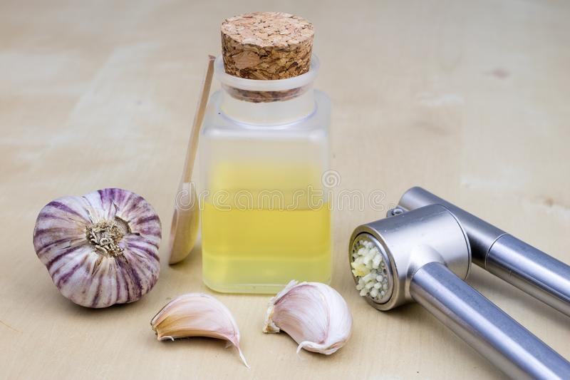A healthy and medicinal garlic syrup squeezed with a kitchen squeezer. Natural methods of treating colds. Light background royalty free stock photography