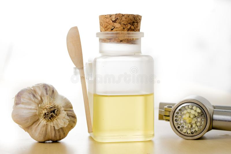 A healthy and medicinal garlic syrup squeezed with a kitchen squeezer. Natural methods of treating colds. Light background stock image