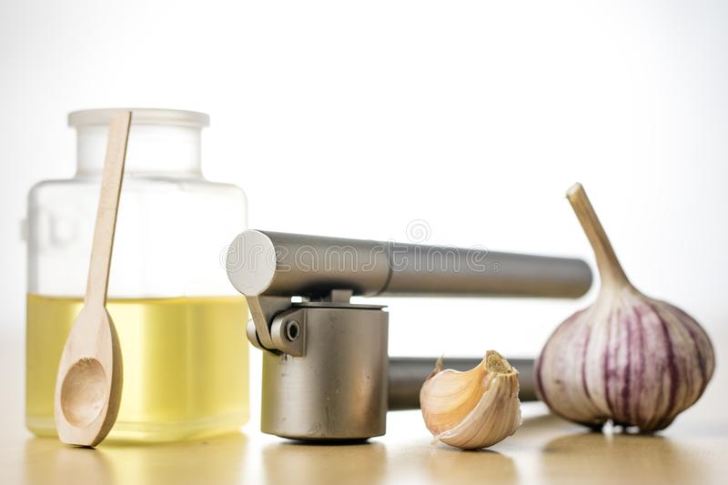 A healthy and medicinal garlic syrup squeezed with a kitchen squeezer. Natural methods of treating colds. Light background stock photography