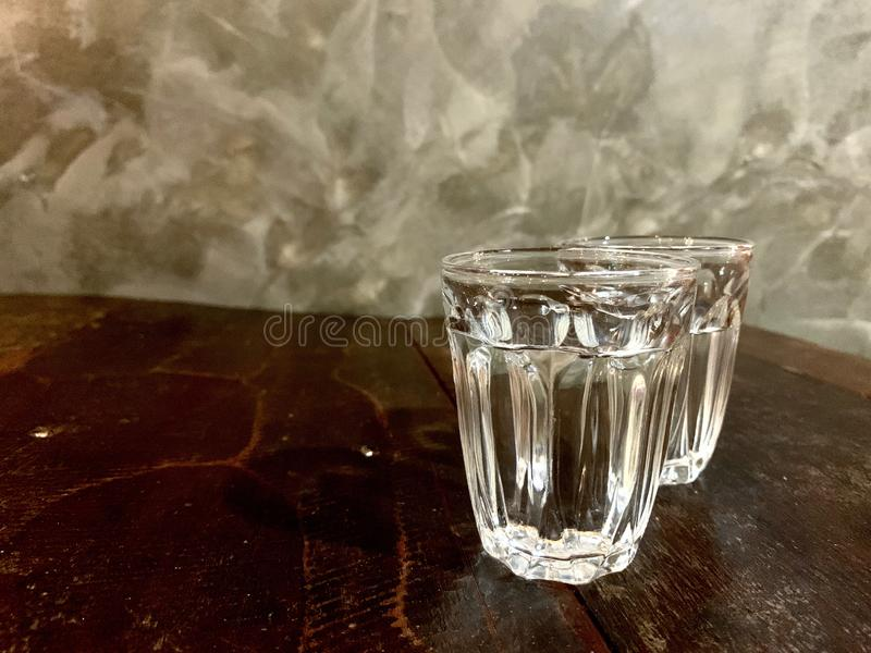 Healthy mineral, clear water in 2 glass on a wooden table, classic and vintage old style royalty free stock images