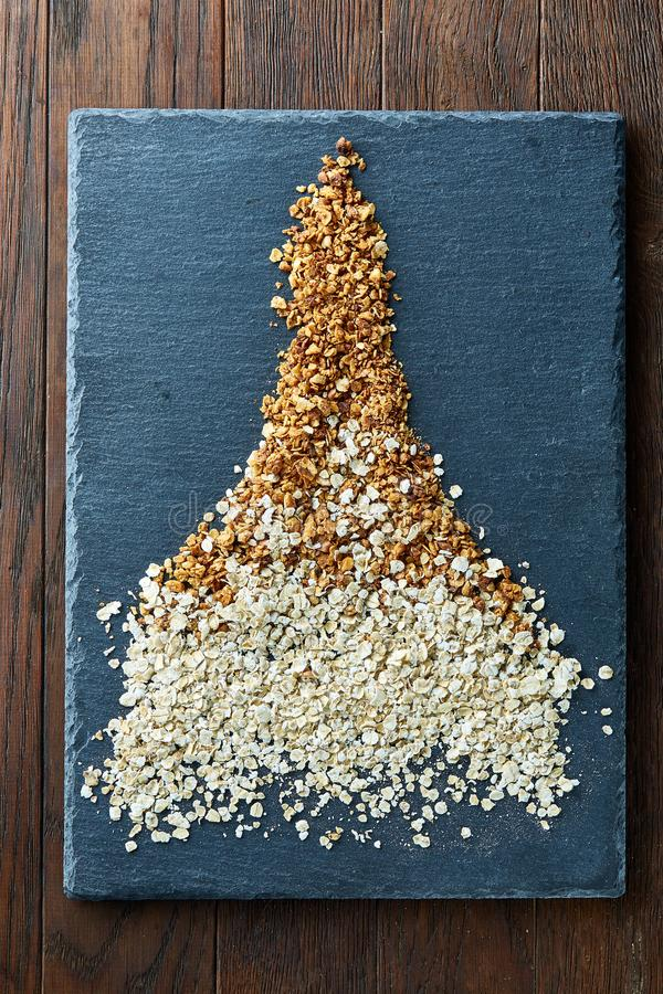 Healthy mix of granola and oatmeal on dark board over wooden background, top view, close-up, selective focus stock images