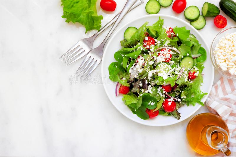 Healthy mixed salad, above scene corner border against a white marble background with copy space stock images
