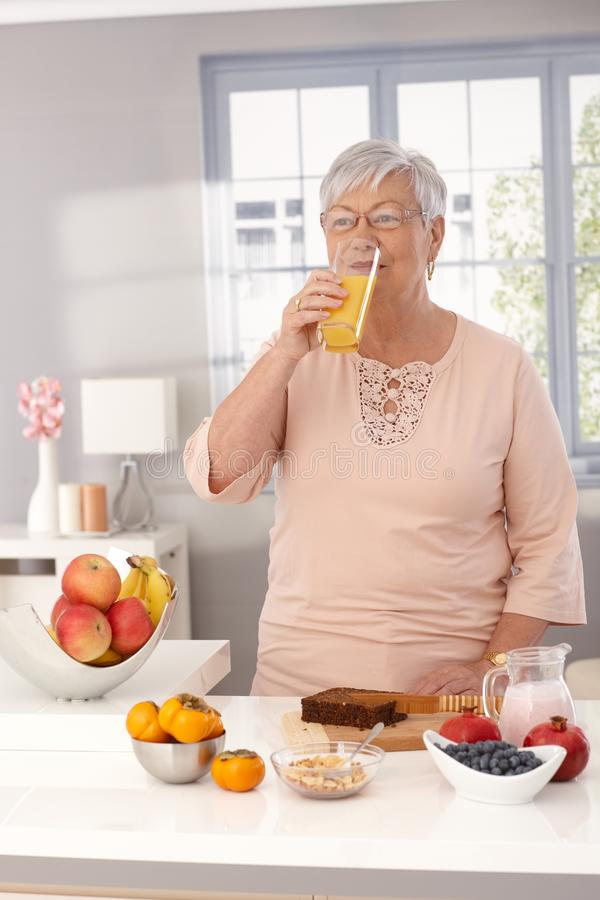 Healthy morning. Granny drinking orange juice in the morning at home while preparing healthy breakfast stock photography