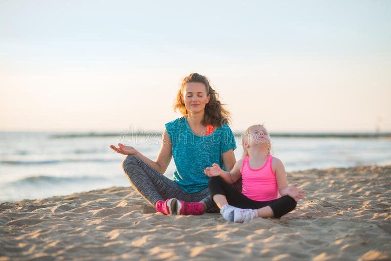 Healthy mother and baby girl doing yoga on beach stock photo