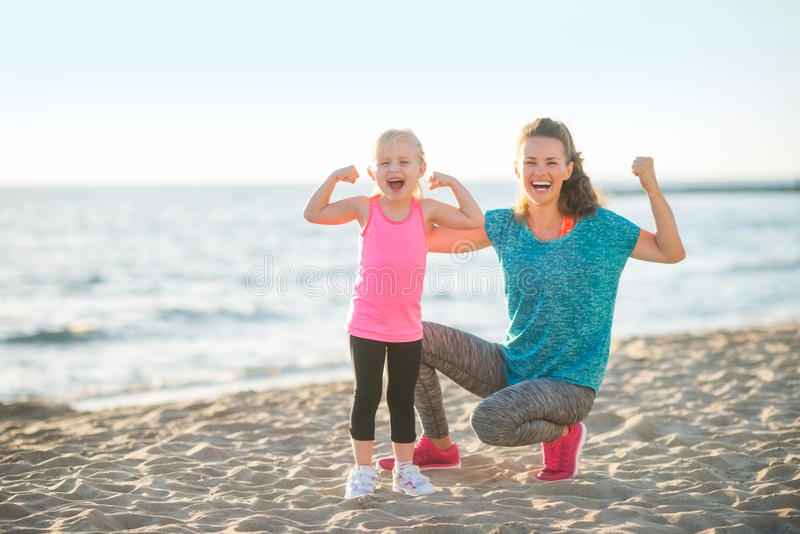 Healthy mother and baby girl showing biceps on bea royalty free stock images