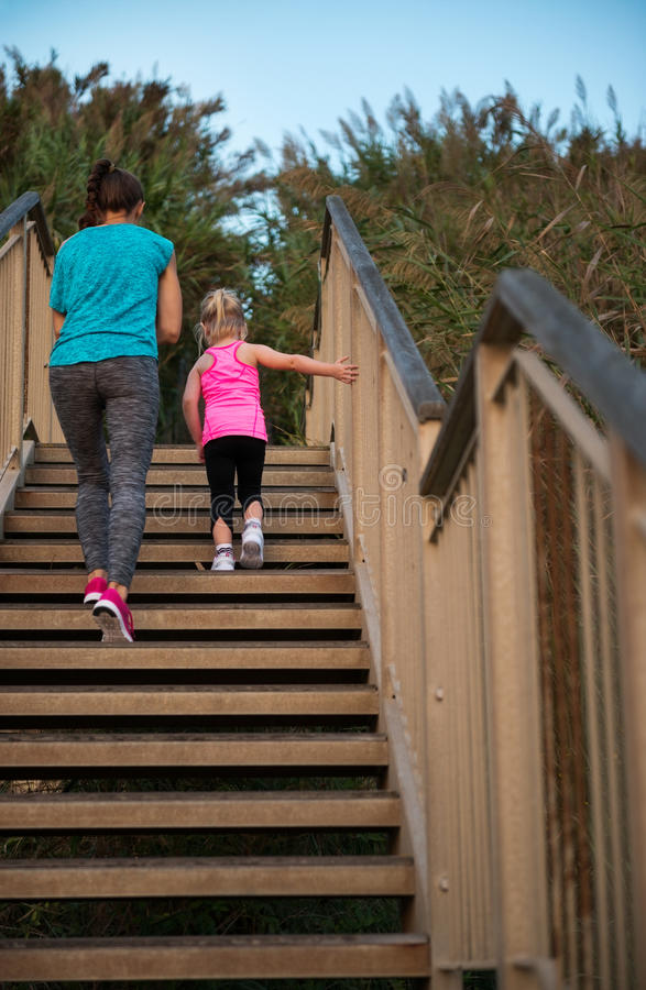 Healthy mother and baby girl walking on stairs royalty free stock photos