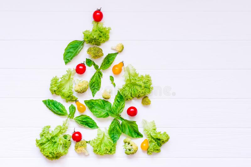 Healthy new year concept - Collection of fresh organic vegetables and greeens in form of christmas tree on white wooden background royalty free stock image