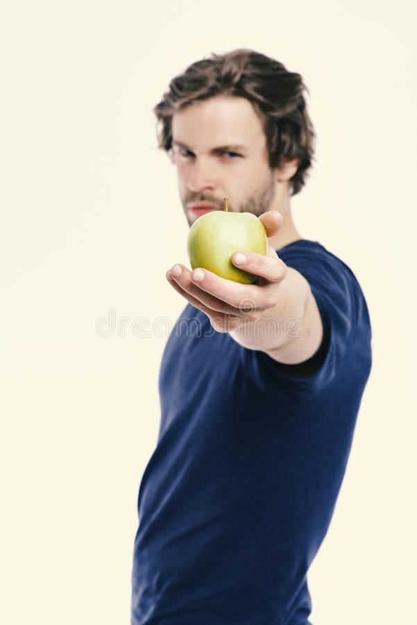 Healthy nutrition and lifestyle concept. Man with bristle holds apple. Guy in blue tshirt. Isolated on white background, defocused. Macho with serious face royalty free stock image