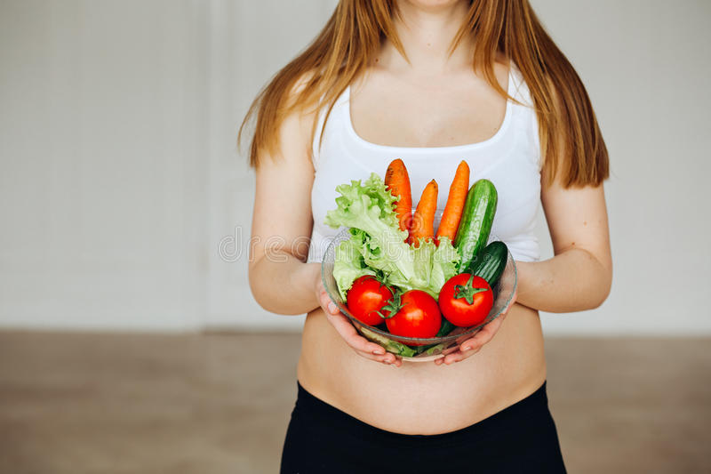Healthy nutrition and pregnancy. Close-up pregnant woman's belly and vegetable salad. A beautiful pregnancy woman eating. Healthy nutrition and pregnancy. Close stock photo