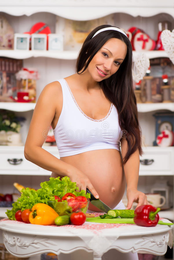 Healthy nutrition and pregnancy. Young smiling pregnant woman cuts vegetables on salad royalty free stock photos
