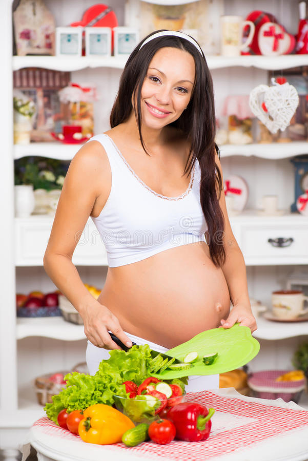 Healthy nutrition and pregnancy. Young smiling pregnant woman cuts vegetables on salad royalty free stock photography