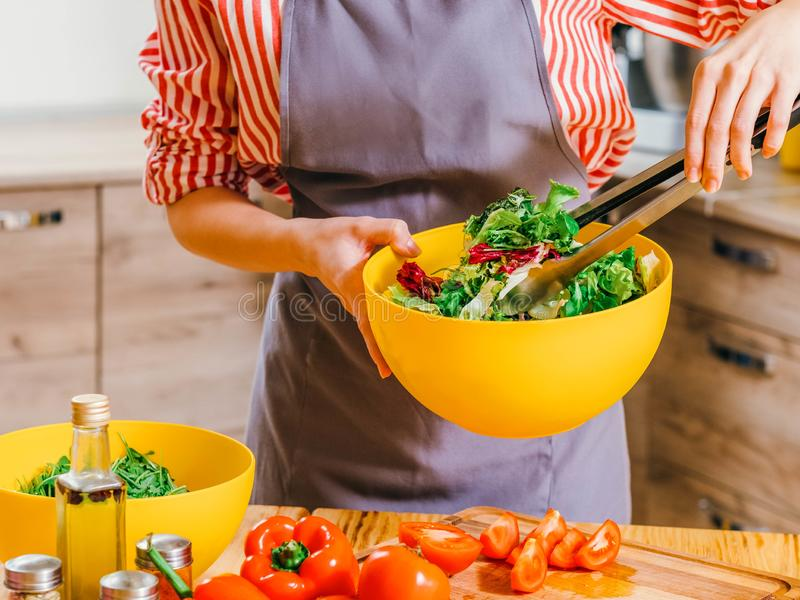 Healthy nutrition woman cooking vegetable salad. Healthy nutrition. Cropped shot of woman cooking, using kitchen tongs to mix vegetable salad in yellow bowl stock photography