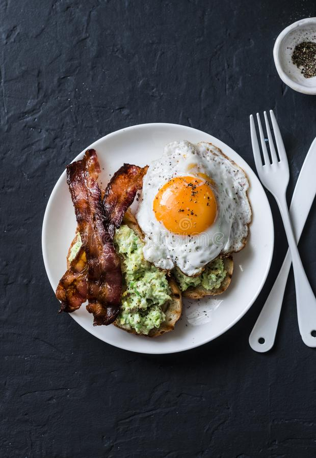 Healthy nutritious breakfast - avocado toast, bacon and fried egg on dark background. Top view royalty free stock photography