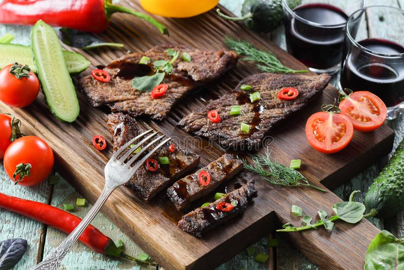 Healthy nutritious meal. Well done beef steak with raw vegetable. S, herbs and wine on oak wood board royalty free stock photo