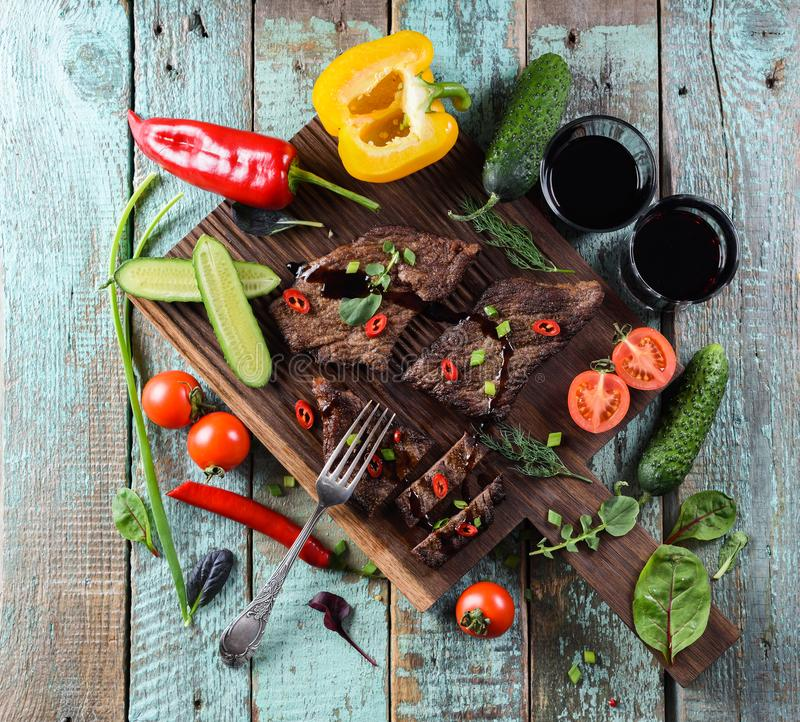 Healthy nutritious meal. Well done beef steak with raw vegetable. S, herbs and wine on oak board on shabby blue wooden background top view stock photography