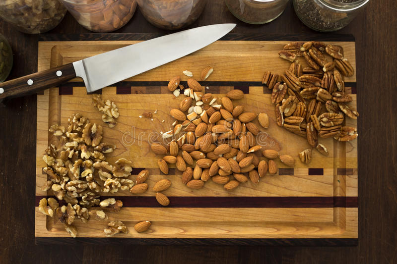 Download Healthy Nuts On Kitchen Cutting Board, With Knife. Stock Photo - Image: 83720694