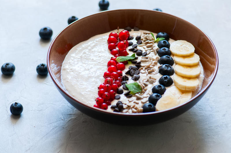 Healthy oat smoothie with bananas and cottage cheese garnished w. Ith red currants, sunflower seeds, chocolate drops and blueberries in a bowl on a white stone stock image