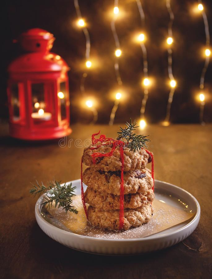 Healthy oatmeal cookies with dried berries on a background of a burning garland royalty free stock image