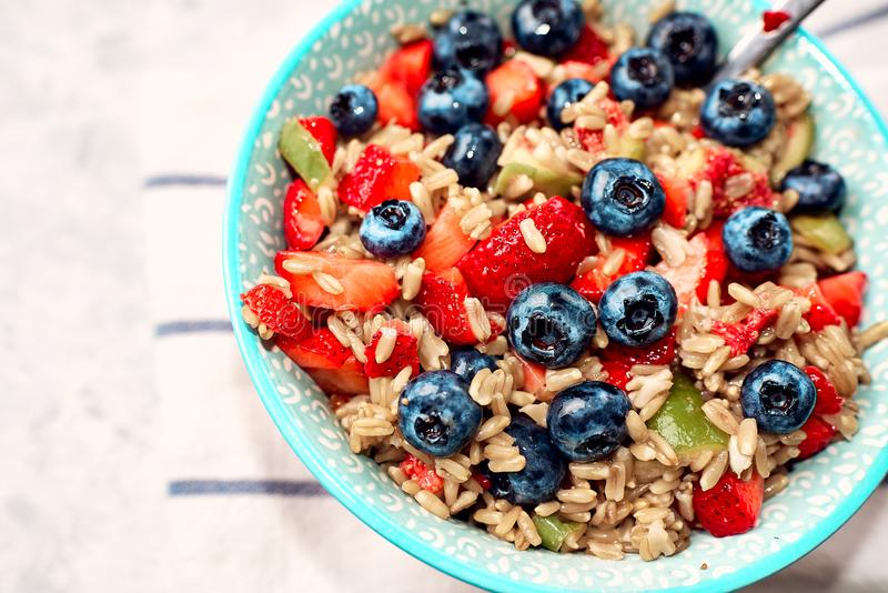 Healthy oatmeal with fruits and berries, strawberries, blueberries and figs in a blue bowl on a gray background for Breakfast royalty free stock image
