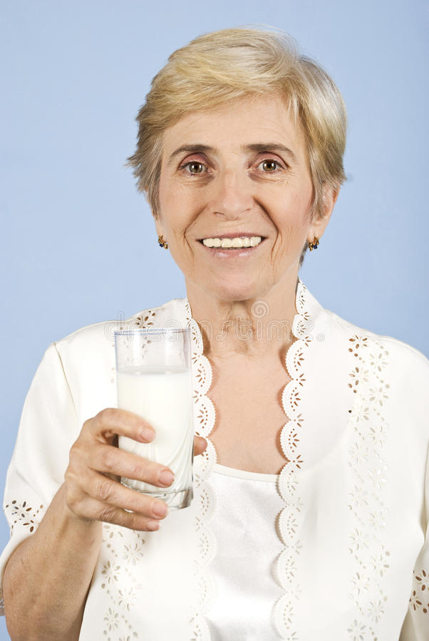 Healthy old woman drinking milk royalty free stock photo