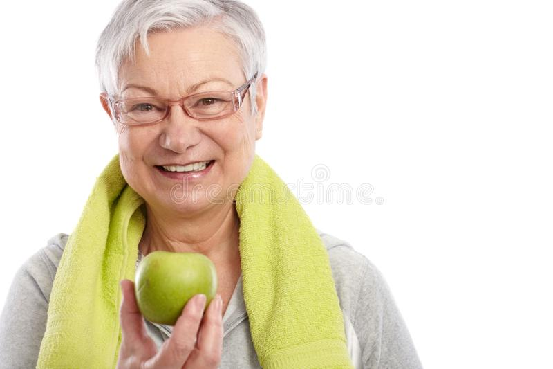 Healthy old woman with green apple smiling stock photo