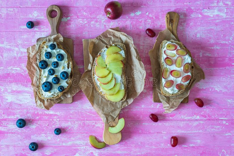 Healthy open sandwiches with fruits ,peach grapes blueberries and soft cheese on pink wooden background royalty free stock photos