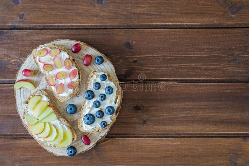 Healthy open sandwiches with fruits ,peach grapes blueberries and soft cheese on wooden background , top view , flat lay stock photo
