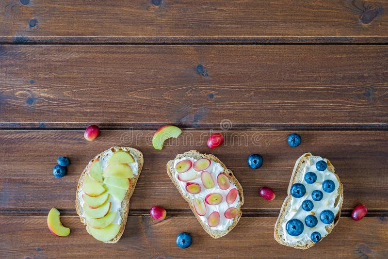 Healthy open sandwiches with fruits ,peach grapes blueberries and soft cheese on wooden background , top view , flat lay stock images