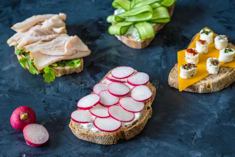 Healthy open sandwiches with vegetables , carrots , radish , cheddar cheese and turkey pastrami, cucumber on a wooden background royalty free stock photography