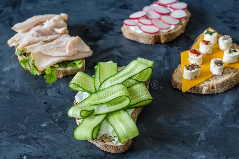 Healthy open sandwiches with vegetables , carrots , radish , cheddar cheese and turkey pastrami, cucumber on a wooden background royalty free stock photo