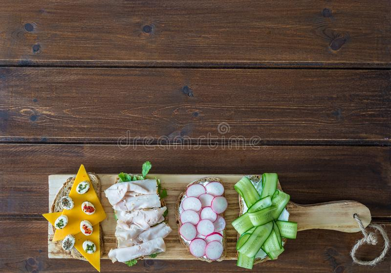 Healthy open sandwiches with vegetables ,cucumber radish turkey pastrami cheddar cheese and soft cheese on wooden background royalty free stock photos